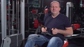 在背部肌肉的工作 由在健身房的划船器是成功的人 锻炼机器的人有的 股票录像