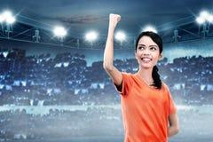 在胜利以后的幸福亚裔足球运动员妇女她的比赛 免版税图库摄影