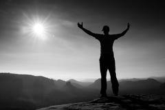 在胜利红色盖帽的愉快的人姿态用手在天空中 砂岩岩石峰顶的滑稽的远足者在萨克森瑞士同水准的 免版税库存图片