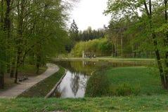 在胡同附近的一条河有放松的长木凳的在一个绿色公园 免版税库存照片