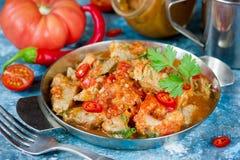 在胡椒西红柿酱的罐装被炖的猪肉 库存图片