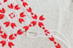 在胡麻的被绣的片段由红色和白色棉花螺纹 宏观刺绣纹理平的针 库存照片