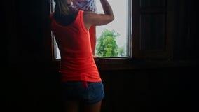 在胳膊白肤金发的女孩的母亲推力显示有雾的小山在窗口外面 股票录像