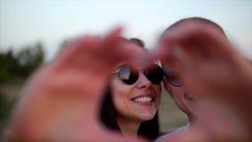 在胳膊的美好的愉快的时髦的快乐的年轻欧洲逗人喜爱的夫妇彼此,做在a的手外面 影视素材
