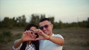 在胳膊的美好的愉快的时髦的快乐的年轻欧洲逗人喜爱的夫妇彼此,做在a的手外面 股票录像