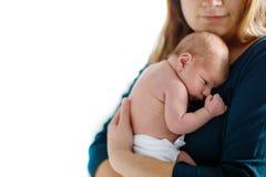 在胳膊的诞生以后照顾拿着她新出生的小女儿 免版税库存照片