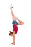 在胳膊的年轻专业体操运动员立场在丝毫 免版税库存照片