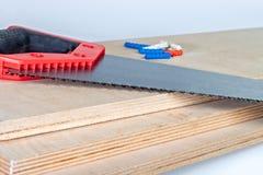 在胶合板板的引形钢锯与定缝销钉 库存照片