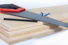 在胶合板板的引形钢锯与色的定缝销钉 图库摄影