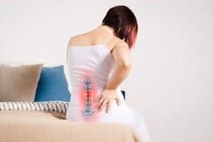 在脊椎的痛苦,妇女以在家腰疼,在低后的伤害 免版税库存照片