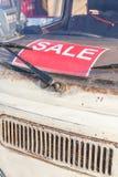 在脏和老半新车挡风玻璃,汽车的红色销售标志 库存图片