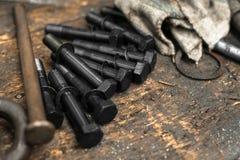 在脏的桌上的黑螺栓 免版税图库摄影