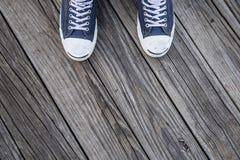 在脚的蓝色帆布运动鞋在木头 免版税库存图片