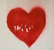 在腐朽的墙壁上的红色心脏 免版税库存照片