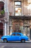 在腐朽的大厦旁边的老汽车在哈瓦那 库存图片