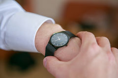 在腕子的人的手表 图库摄影
