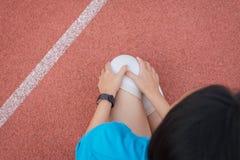 在腿的运动员亚洲妇女痛苦有脚腕的在室外跑跑步和的锻炼以后被伤害 免版税库存图片