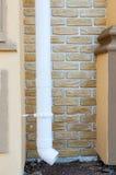 在膏药墙壁上的新的雨天沟有装饰砖的 设施白色雨天沟特写镜头 图库摄影