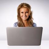 在膝上型计算机之后的微笑的妇女 库存图片