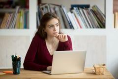 在膝上型计算机前面的体贴的年轻女性企业家 免版税库存图片