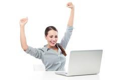 在膝上型计算机前面的妇女有被举的胳膊的 免版税库存图片