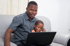 在膝上型计算机前面的愉快的家庭 免版税库存照片