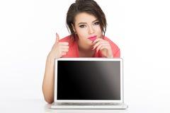 在膝上型计算机后的妇女有拇指的 图库摄影