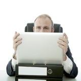在膝上型计算机和文件之后的商人隐藏 免版税库存照片