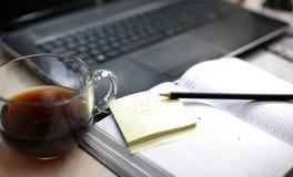 在膝上型计算机和日志附近的早晨咖啡 免版税库存图片