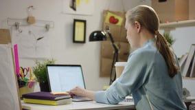 在膝上型计算机和饮料咖啡的年轻女人工作 股票视频