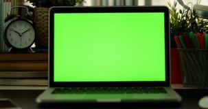 在膝上型计算机外面的移动式摄影车有绿色屏幕的 黑暗的办公室 完善投入您自己的图象或录影 使用的技术绿色屏幕  影视素材