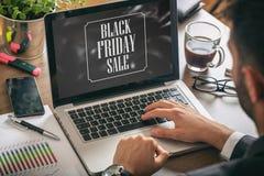 在膝上型计算机屏幕上的黑星期五销售文本,办公室背景 免版税库存图片