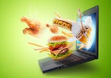 在膝上型计算机屏幕外面的食物飞行 库存图片