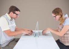 在膝上型计算机的书呆子夫妇反对棕色背景 库存照片