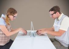 在膝上型计算机的书呆子夫妇反对棕色背景 免版税库存照片