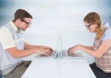 在膝上型计算机的书呆子夫妇反对模糊的蓝色木盘区 免版税库存图片