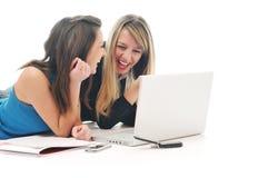 在膝上型计算机的二个女孩工作 免版税库存照片