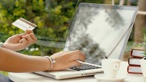 在膝上型计算机的亚洲妇女键入和交易信用卡 图库摄影