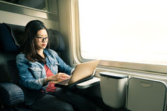 在膝上型计算机的亚洲妇女工作在火车,商务旅游概念,温暖的轻的口气 免版税图库摄影
