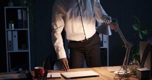 在膝上型计算机的商人完成的工作和离开从办公室在晚上 股票视频