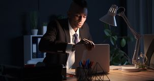 在膝上型计算机的商人完成的工作和离开办公室在晚上 股票录像