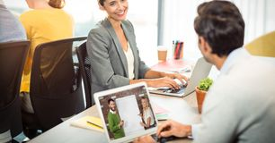 在膝上型计算机的商人视讯会议,当看同事在办公室时 免版税图库摄影