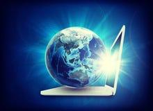 在膝上型计算机的地球模型,侧视图 免版税图库摄影
