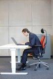 在膝上型计算机的坏坐姿在他的办公室.short看见了椅子的商人 库存照片