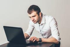 在膝上型计算机的大忙人工作在办公室 商人集中于任务的解答 免版税库存图片