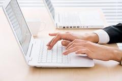 在膝上型计算机的女性手 免版税库存图片