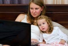 在膝上型计算机的妇女和小女孩注意的动画片 免版税库存照片