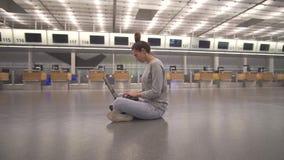 在膝上型计算机的妇女工作和等待的飞行在机场在地板上的终端 影视素材
