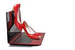 在膝上型计算机的妇女红色鞋子 库存照片