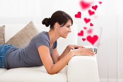 在膝上型计算机的妇女约会在家 免版税库存照片